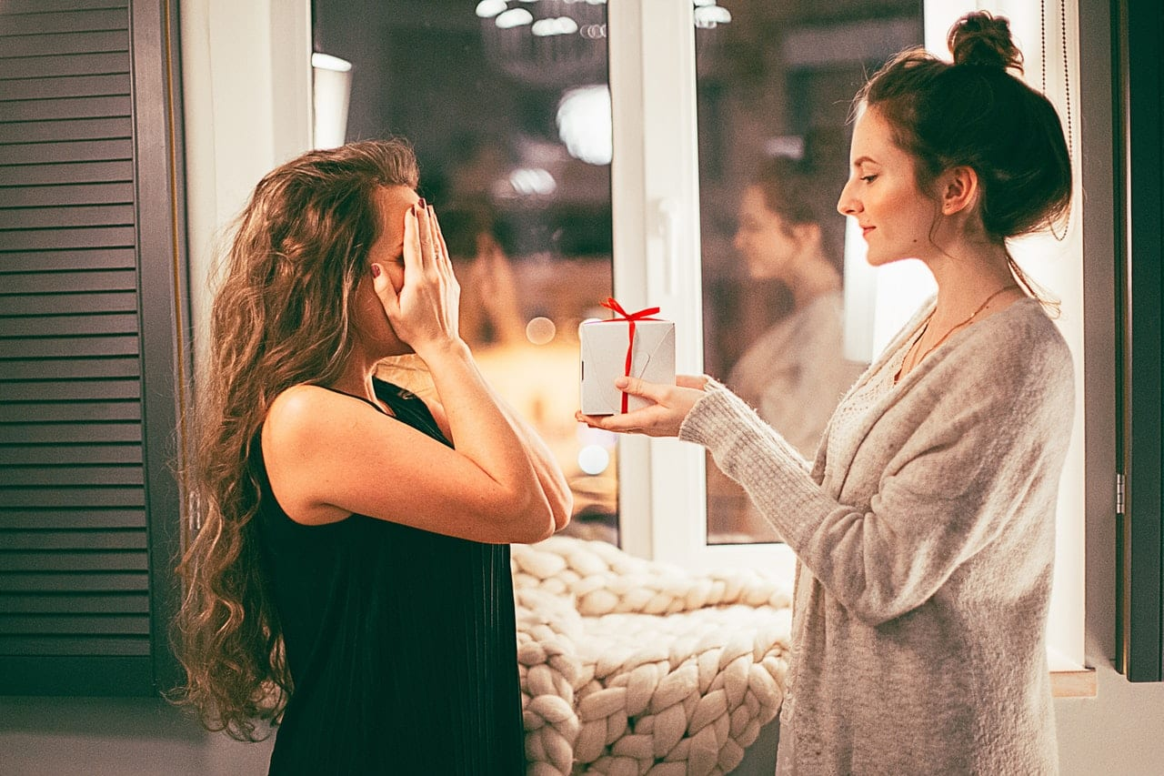 woman giving house warming gifts to another woman