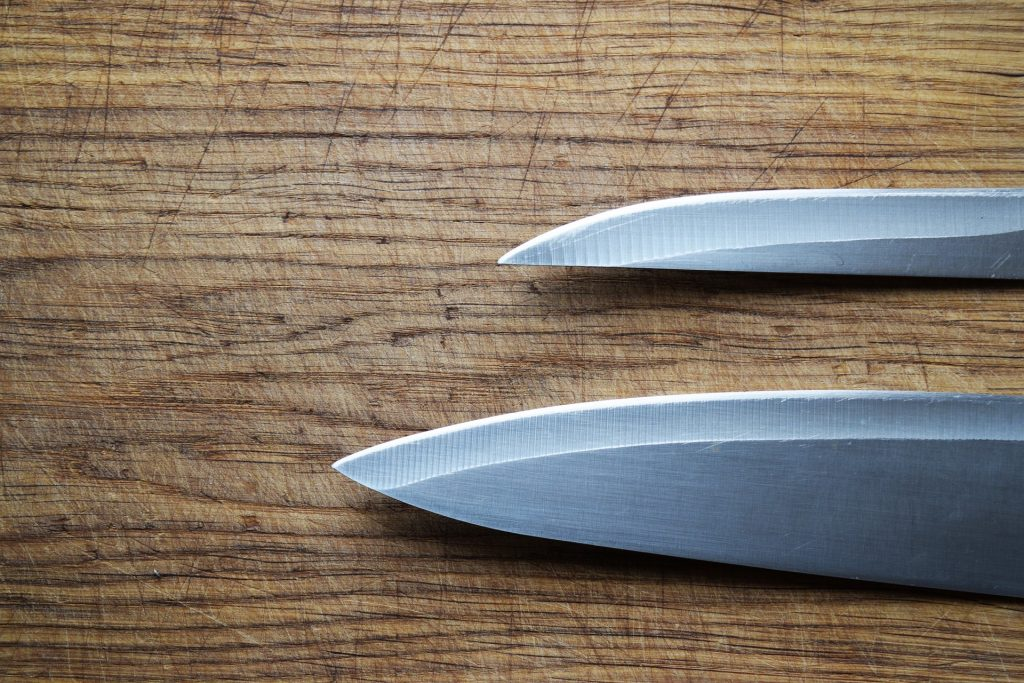 2 kitchen knives on a cutting board